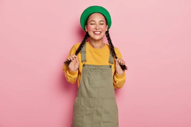 귀여운 겸손한 십대 소녀가 두 개의 땋은 머리를 잡고 긍정적 인 삶의 순간을 즐기고 녹색 베레모와 사라 판을 입고 코를 뚫었습니다.