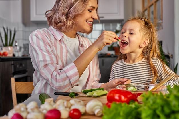Милая мама и дитя дегустируют свежие фрукты, готовят салат на ужин, вместе нарезают его