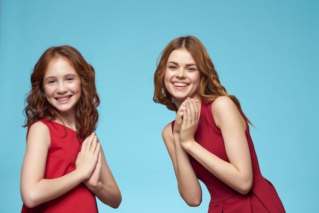 빨간 드레스를 입은 귀여운 엄마와 딸 재미있는 매력 스튜디오