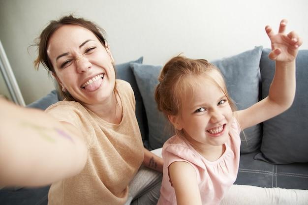 Симпатичные мама и дочь делают селфи и дурачатся в камере телефона.