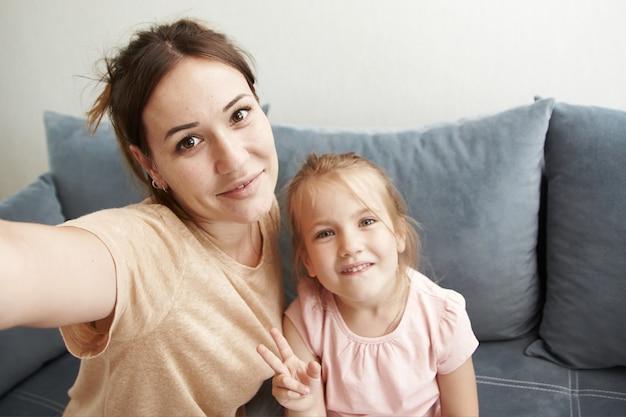 かわいいお母さんと娘は自分撮りをして、携帯電話のカメラで笑顔します。