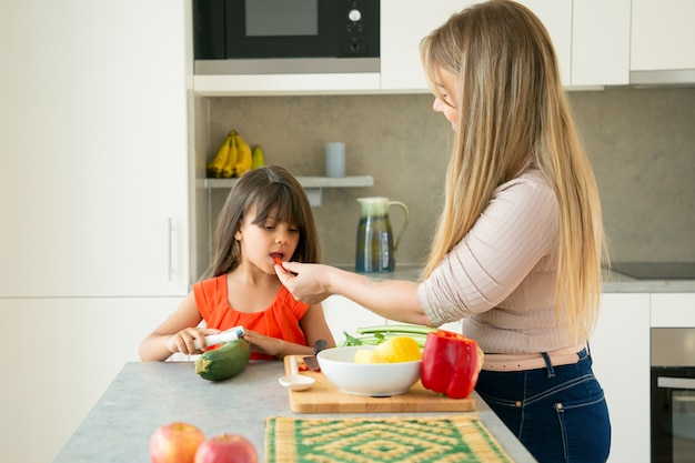 Cute mom and daughter cooking salad for dinner together, cutting vegetables on kitchen counter, tasting slice of pepper. medium shot. family cooking concept