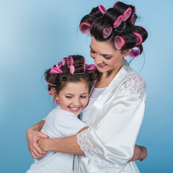 Cute mother and daughter in curlers hugging