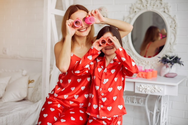 Cute mother and daughter at home in a pajamas
