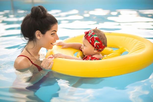 Милая мама плавает в бассейне с ребенком