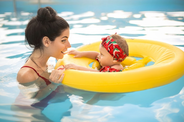 Cute mother swimming in the swimming pool with her baby