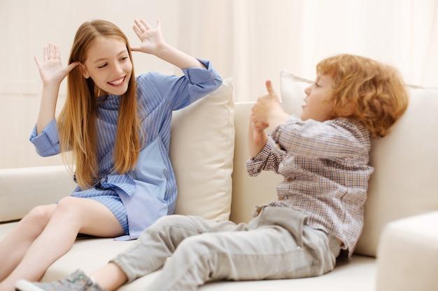 집에서 함께 시간을 보내는 동안 소파에 앉아 주위에 노는 귀여운 운동 에너지 어린이