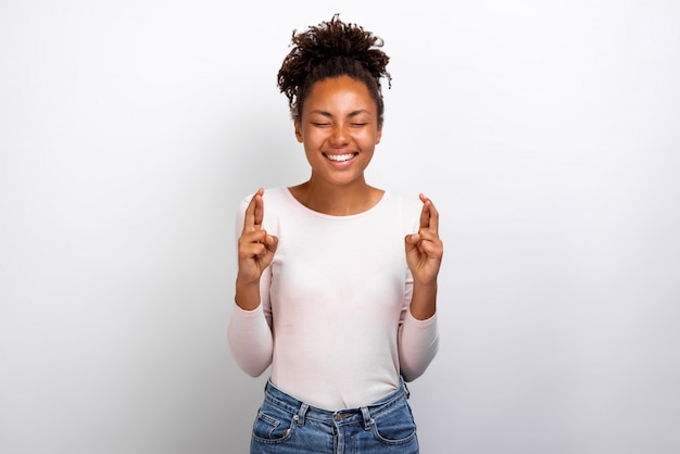 Cute mulatto woman crossing her fingers and wishing for good luck