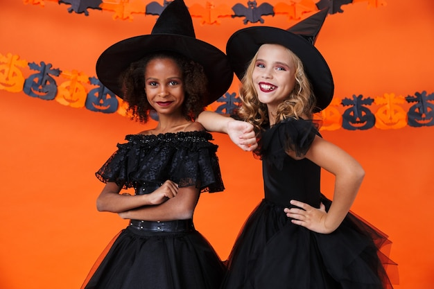 Cute multinational girls in black halloween costumes smiling and standing together isolated over orange pumpkin wall