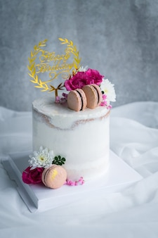 Cute naked cakes decorated with macaron and rose flower on white cloth background. modern cake and bakery concept