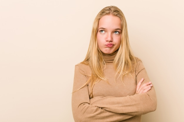 Cute and natural teenager woman frowning face in displeasure, keeps arms folded.