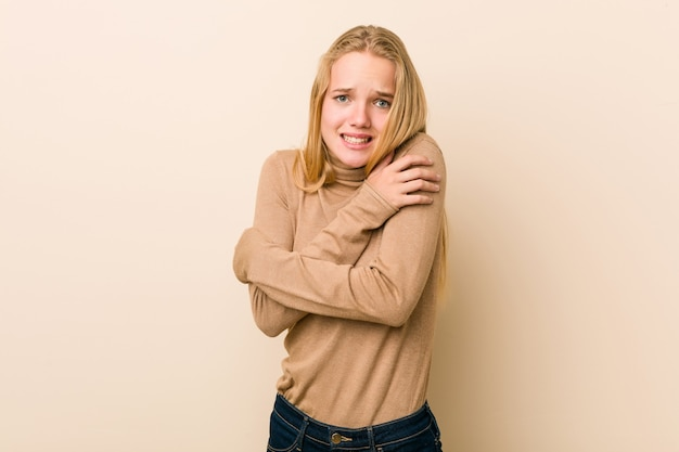 Cute and natural teenager woman going cold due to low temperature or a sickness.