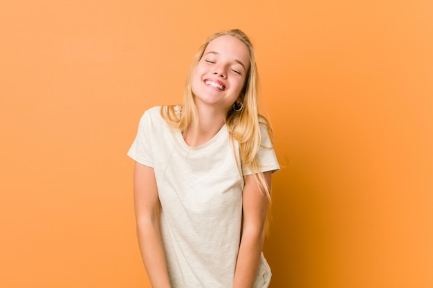 Cute and natural teenager woman laughs and closes eyes, feels relaxed and happy.