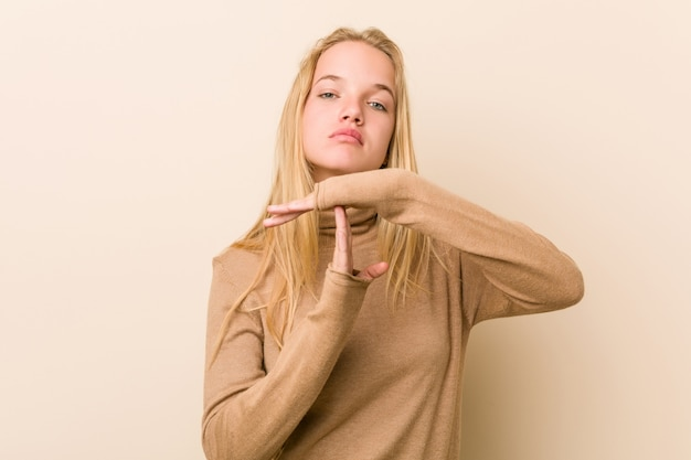 Cute and natural teenager woman showing a timeout gesture