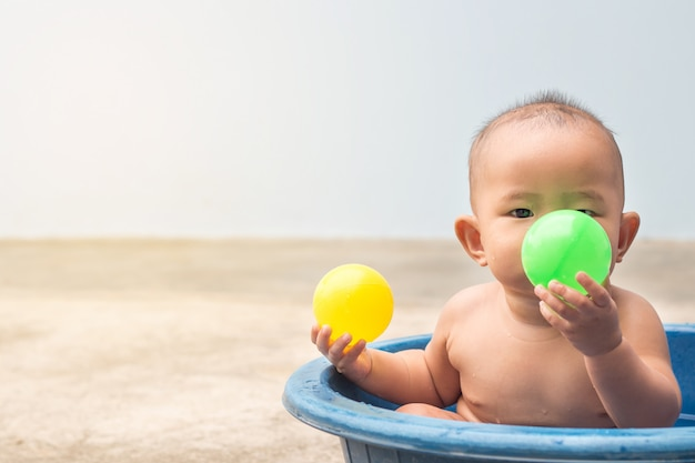 Cute new born baby playing ball in the plastic basin during shower