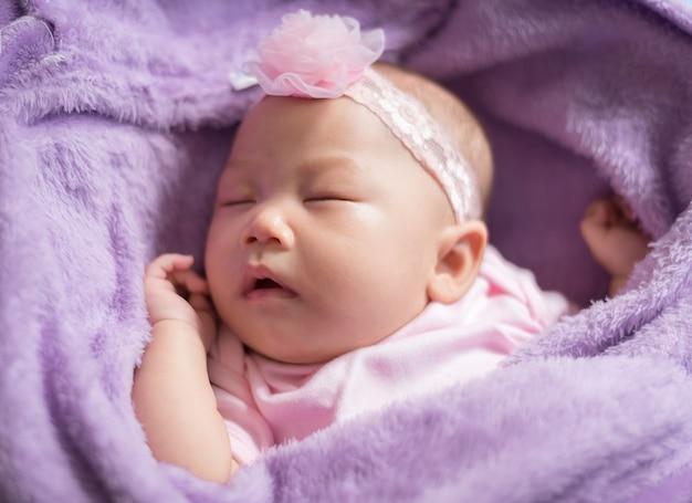ピンクの花のヘッドバンドを身に着けている毛皮のような布で寝ているかわいい新生児アジアの女の子