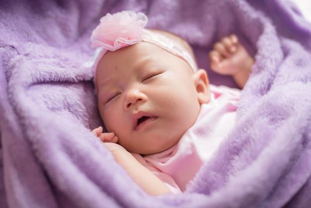 ピンクの花のヘッドバンドを身に着けている毛皮のような布で寝ているかわいいアジアの新生児の女の子。