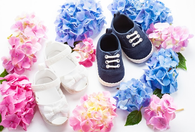 Cute newborn baby boy and girl shoes with hortensia flowers decoration.