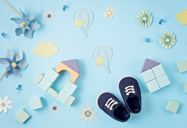 Cute newborn baby boy shoes with festive decoration over blue background
