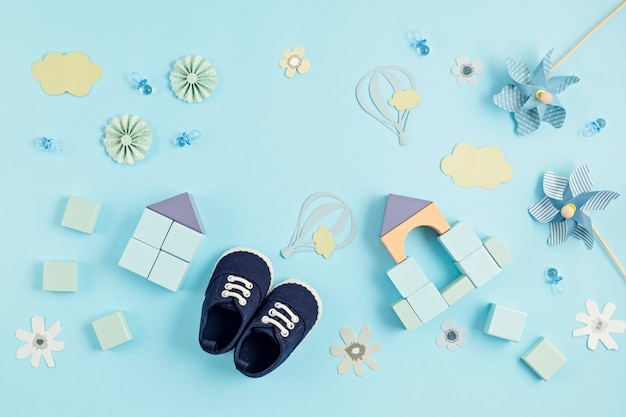 Cute newborn baby boy shoes with festive decoration over blue wall.