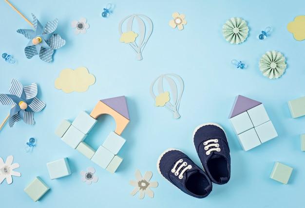 青い背景の上にお祝いの装飾が施されたかわいい新生児男の子の靴