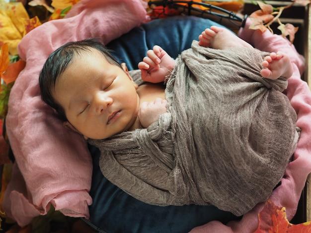 Милый новорожденный мальчик спит в коричневом одеяле, концепция младенцев и новой жизни.