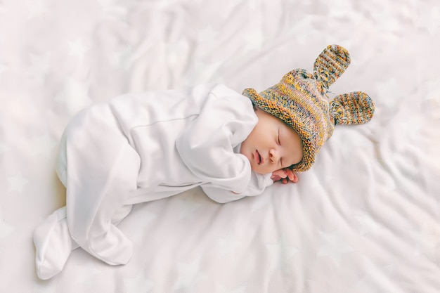 Cute newborn baby in a funny hat with bunny ears is sleeping sweetly in a crib on a white soft sheet, close-up, top view