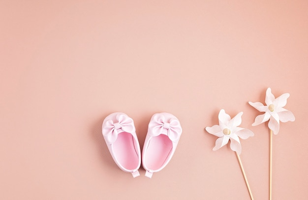 Cute newborn baby girl shoes with festive decoration over pink wall.