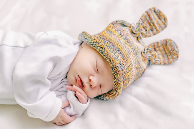 ベビーベッドで甘く眠っているバニーの耳を持つ面白い帽子のかわいい新生児