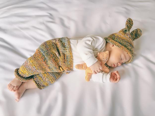 バニーの耳を持つ面白い帽子をかぶったかわいい新生児は、白い柔らかいシート、クローズアップ、上面図のベビーベッドで甘く眠っています