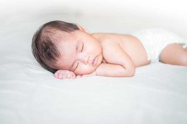 Cute newborn baby is sleeping on white bed