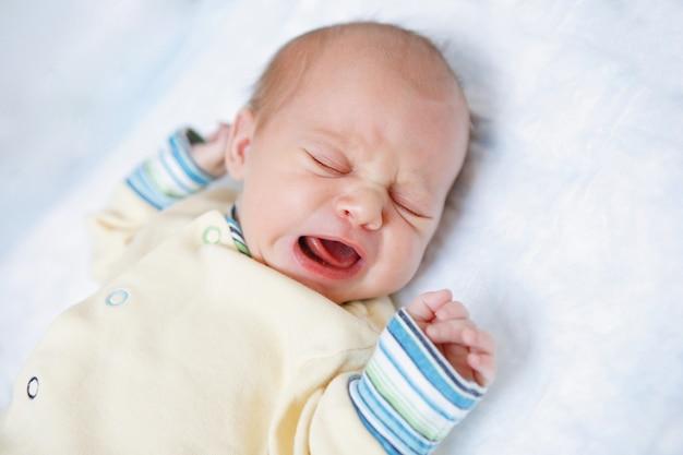 Милый новорожденный ребенок лежит и плачет. счастливое детство. родительская забота.