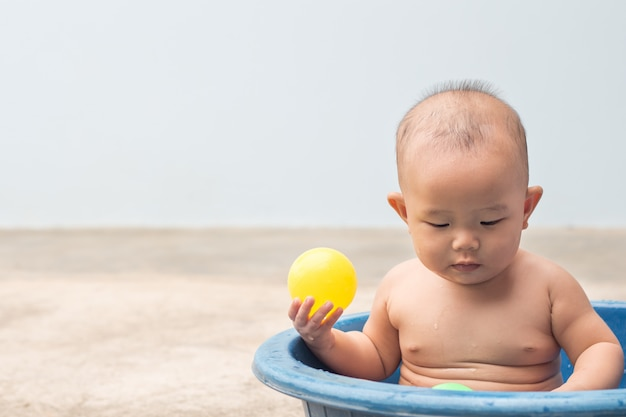 Cute newborn baby playing ball in the plastic basin during shower