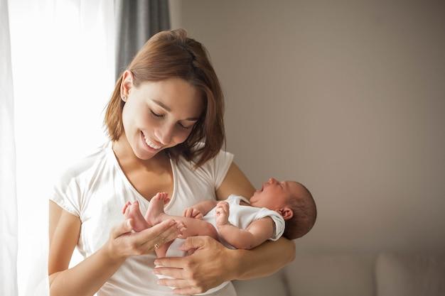 어머니의 팔에 잠자는 귀여운 신생아. 어머니.