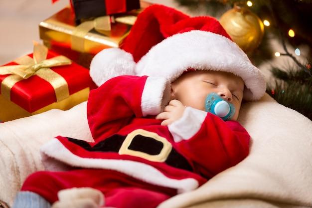 Милый новорожденный ребенок спит в бело-красном костюме санта-клауса