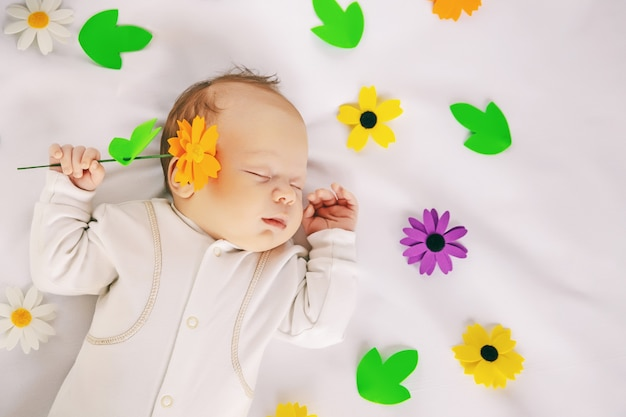 Cute newborn baby sleeping sweetly in crib on white soft sheet with colorful flowers