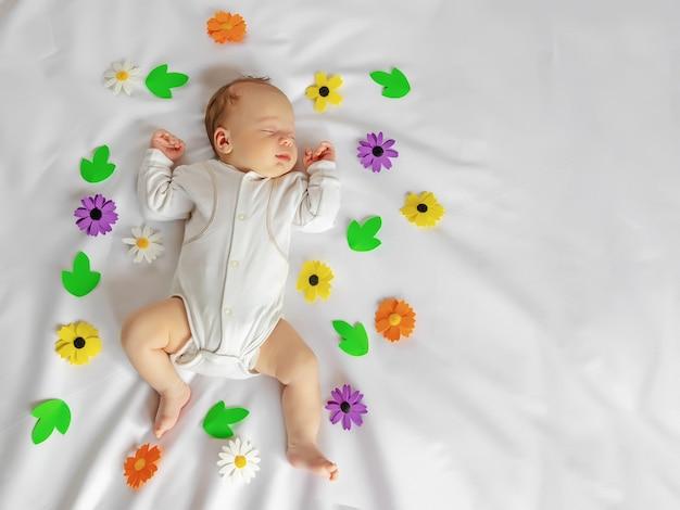 カラフルな花、人生の子供たちの花、幸せな子供時代の赤ちゃん、上面図と白い柔らかいシートのベビーベッドで甘く眠っているかわいい新生児