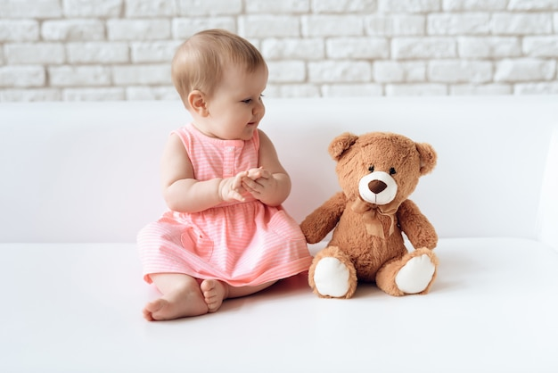 Cute newborn baby on sofa with plush bear