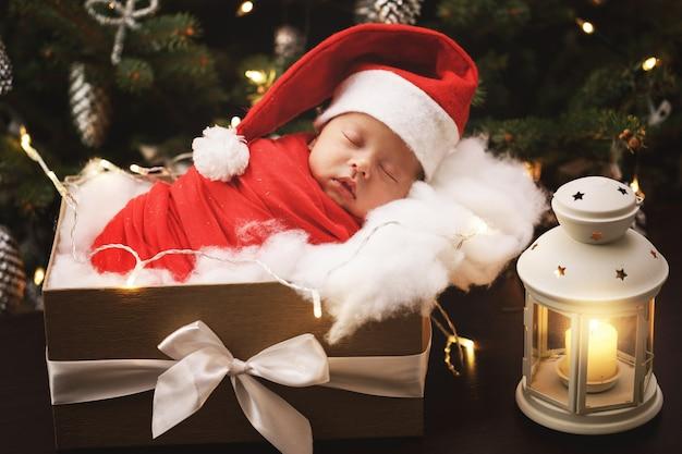 サンタクロースの帽子をかぶったかわいい新生児がクリスマスギフトボックスで眠っています。メリークリスマス、そしてハッピーニューイヤー。