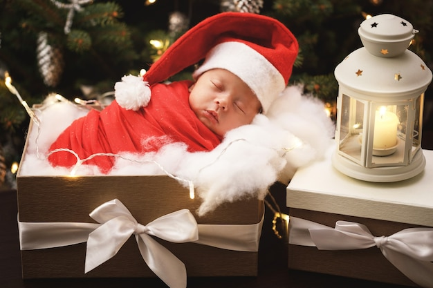 Cute newborn baby wearing santa claus hat is sleeping in the xmas gift box. merry christmas and happy new year.