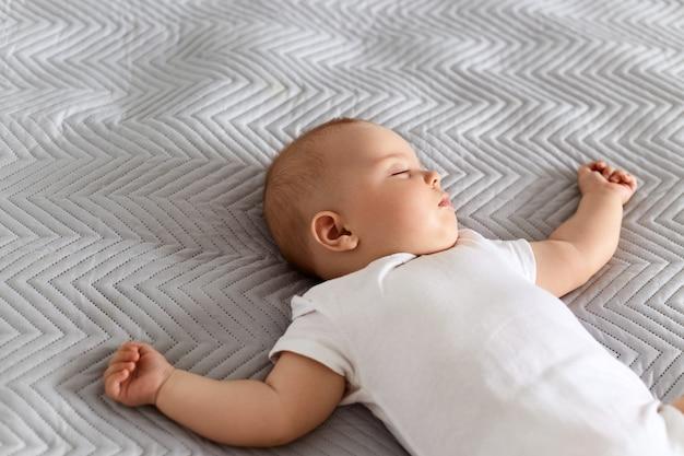 흰색 바디수트를 입은 귀여운 신생아는 회색 담요 위에 침대에 누워 있고, 매력적인 아기는 산책 후 집에서 휴식을 취합니다.