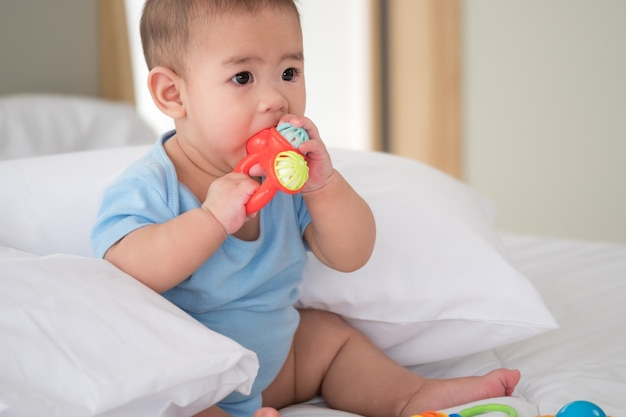 Cute newborn baby with toys in a bedroom.