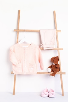 Cute newborn clothes hanging on the rack