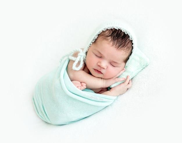 Милый новорожденный спит на крошечной подушке