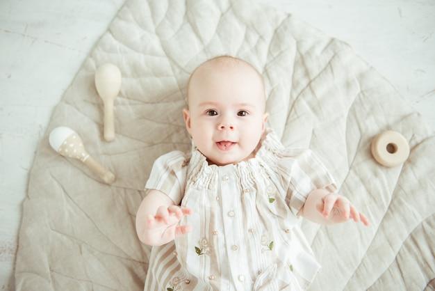 Милый новорожденный малыш, лежащий на бежевом коврике с игрушками из натурального дерева, вид сверху
