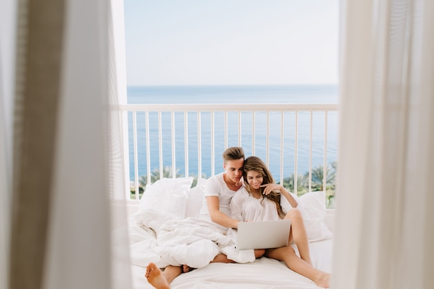 Cute newlyweds in white clothes sitting on bed and watching wedding photos on laptop. portrait of cheerful guy resting on terrace with his gorgeous girlfriend with curtains on foreground