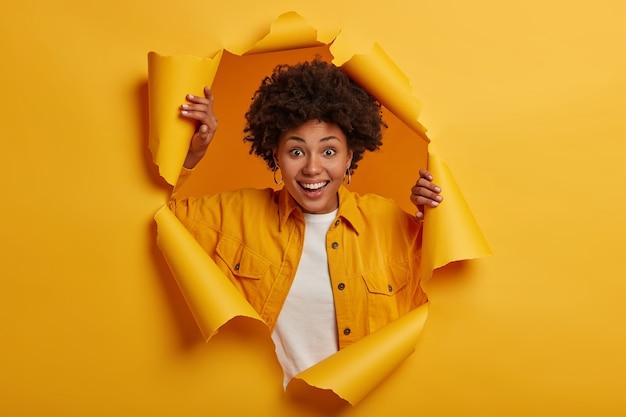 귀여운 멋진 곱슬 머리 아가씨가 재미 있고, 종이 구멍에 포즈, 무료 사진