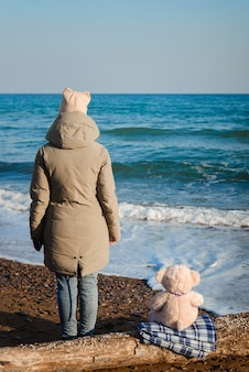 Cute nice girl with a teddy bear in her hands walking on the seashore