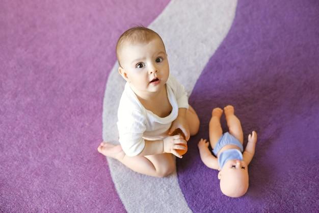 Милая милая маленькая женщина младенца сидя на фиолетовом ковре с куклой.