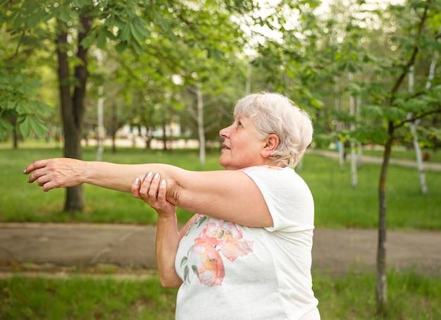 屋外で運動しているかわいい老人白人女性。ヨガを練習している成熟した女性。